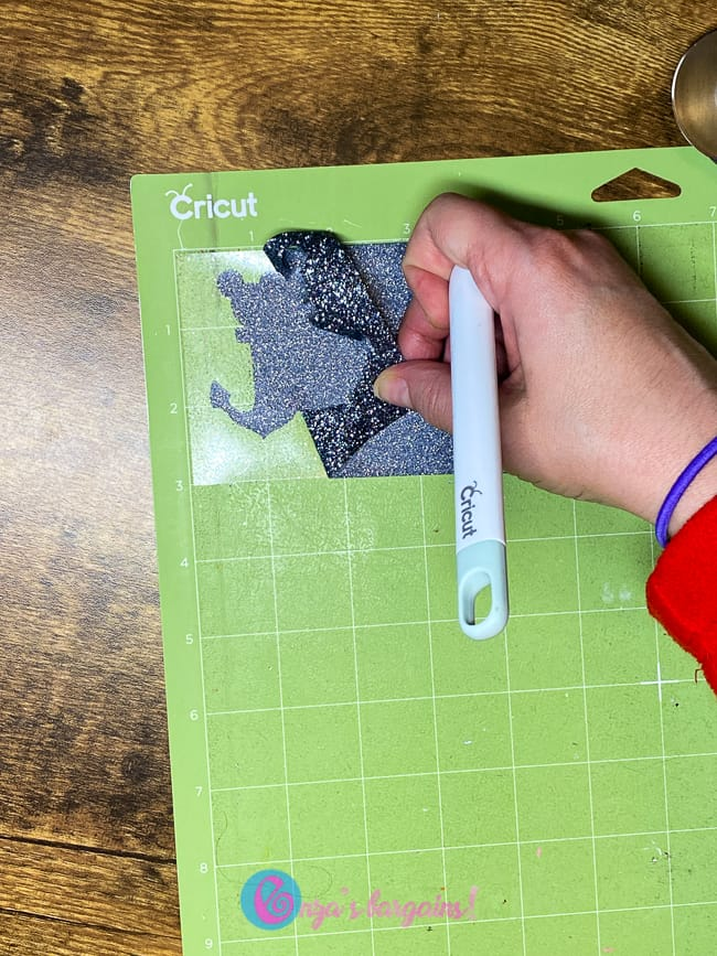 Weeding Glitter HTV Vinyl to apply to a Frame as a Disney Fish Extender Gift.